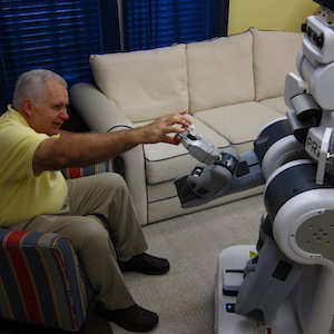 Older man interacting with a robot