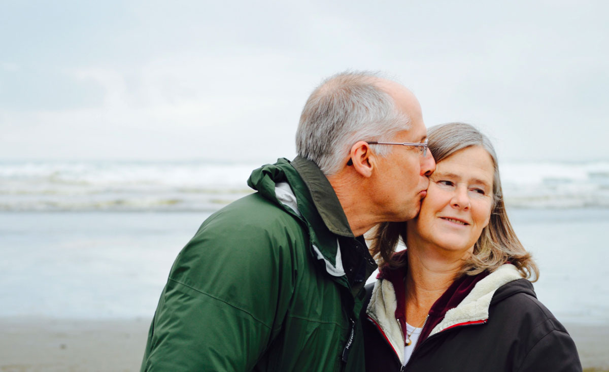 older man kissing older woman on cheek