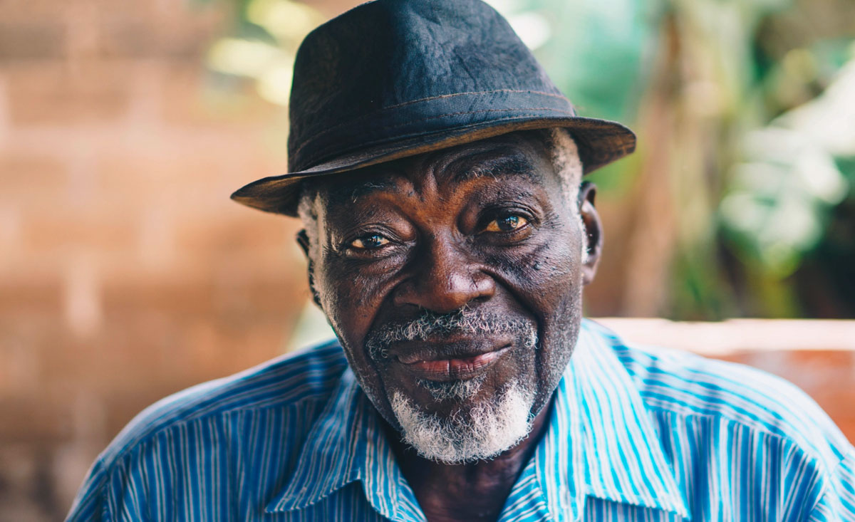 elderly smiling man wearing a hat