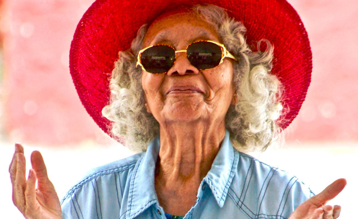 elderly woman wearing a bright red hat